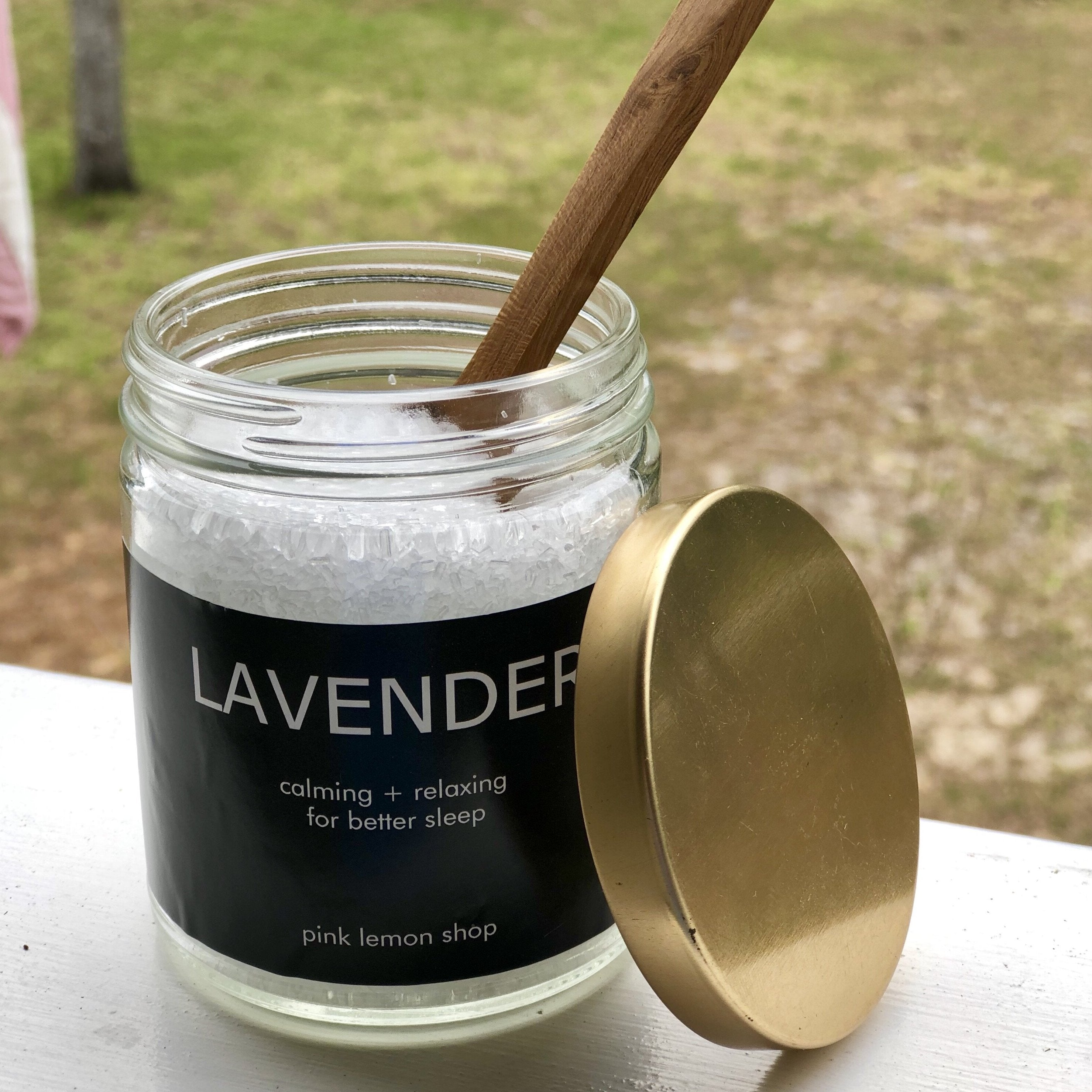 Lavender smelling bath salt in a glass jar with a wooden spoon