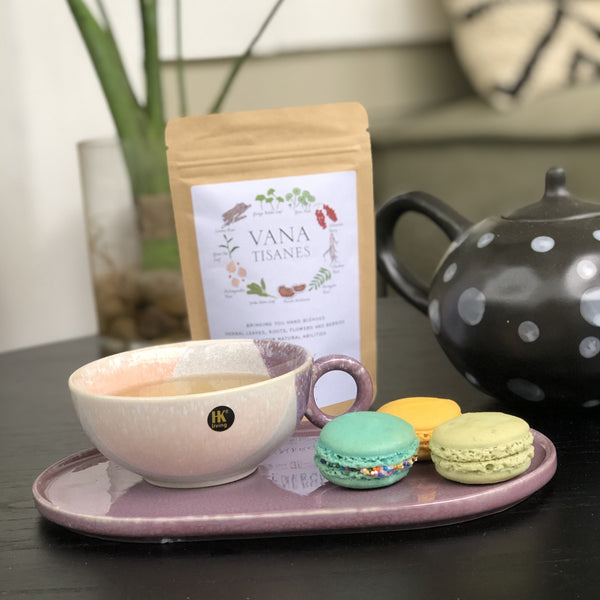 pastel colored cup with tea, macrons and vana tisanes tea