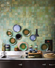 kitchen with green backsplash and stack of 70's ceramics by hkliving usa