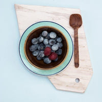 wooden spoon on marble plate with bowl of blueberries