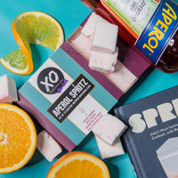 aperol spritz infused marshmallows in a box surrounded by orange slices
