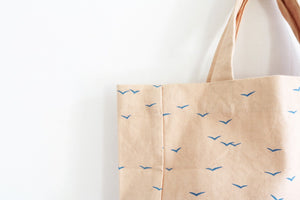 detail of cotton bag in nude with blue birds