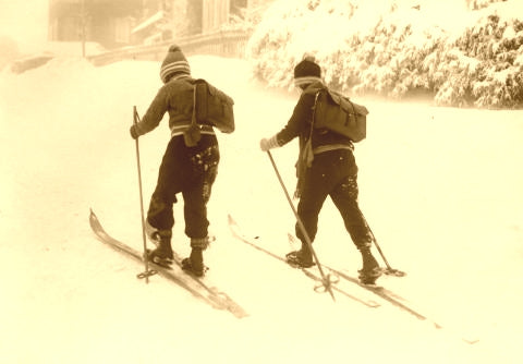 Two kids on old wooden skis.