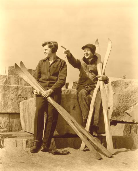 Two kids with old wood skis.