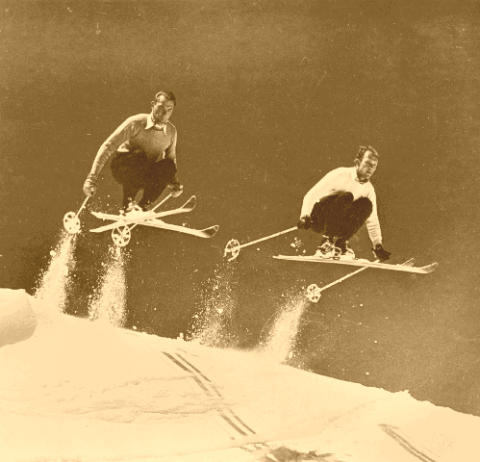 Two skiers catching air on antique skis.