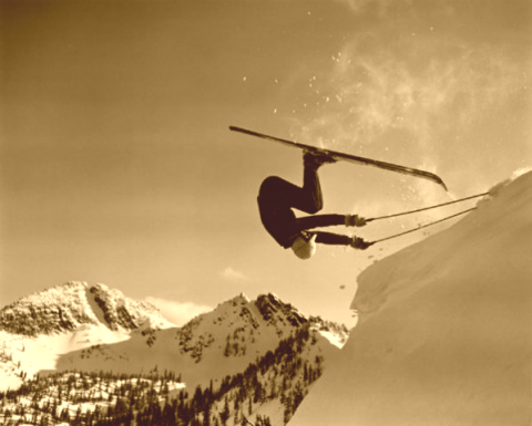 Front flip off a cornice on antique skis.