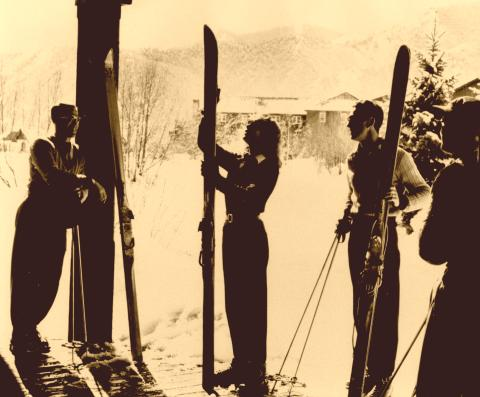 Girl waxing a set of old wood Northland skis