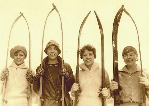 Girls with old wood skis.