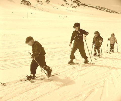 Group of kids skiing on vintage skis.