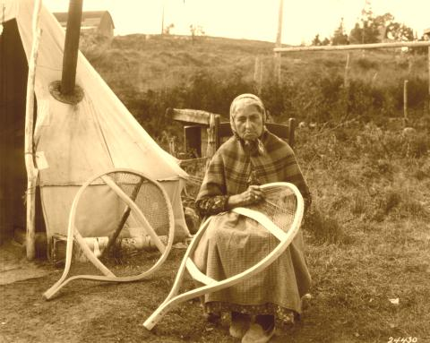 Native American woman weaving snowshoes.
