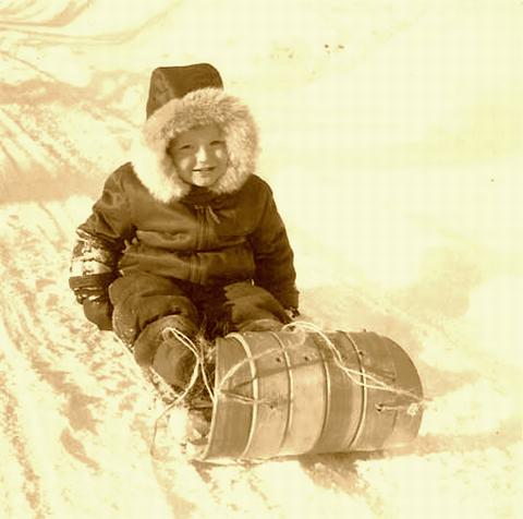 Young child on a old wood Toboggan.