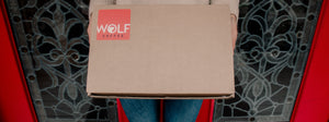 Wolf Coffee delivery package held up by a customer standing in front of door.