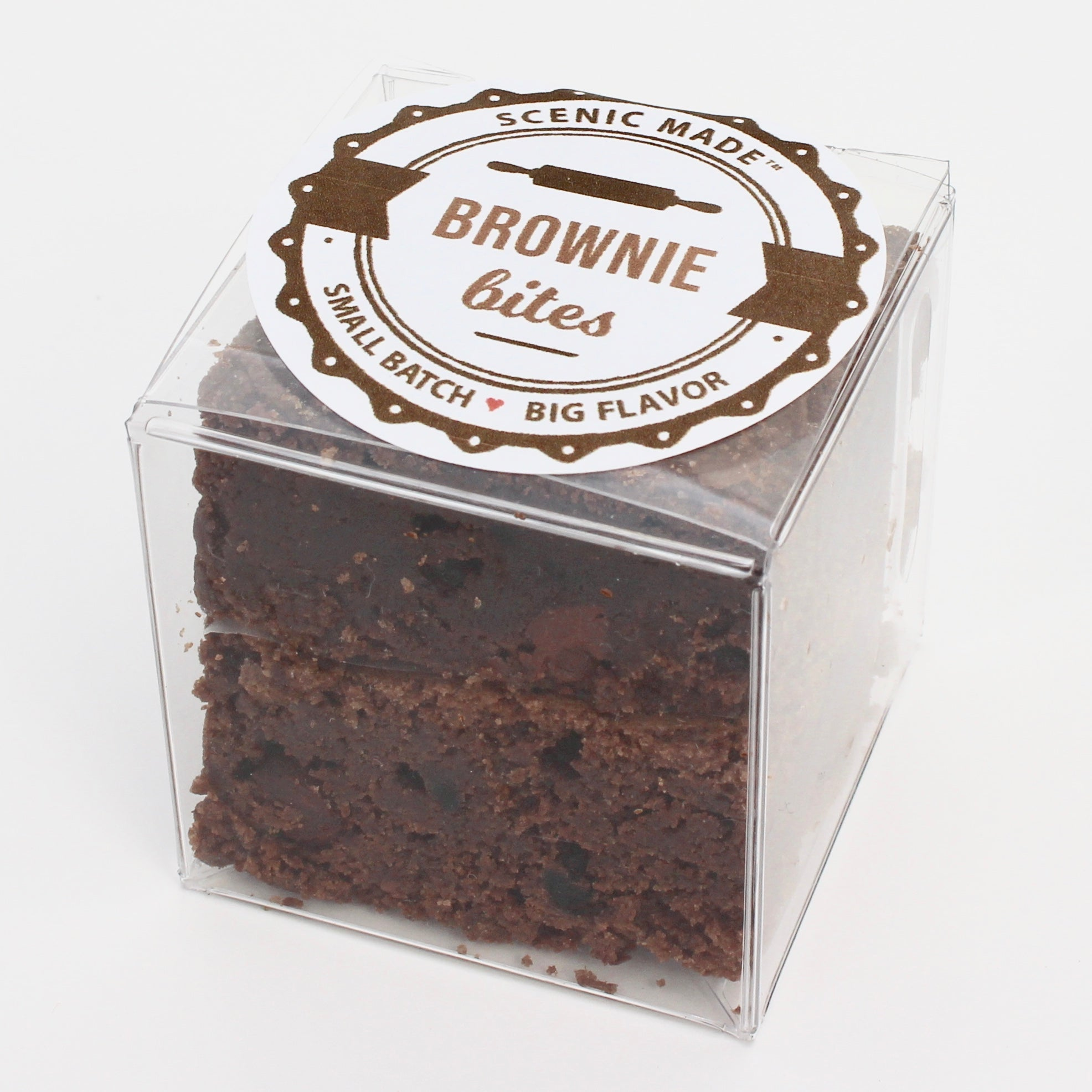 2 decadent brownie bites, packed in a clear, square, food-safe container with an attractive label on top.