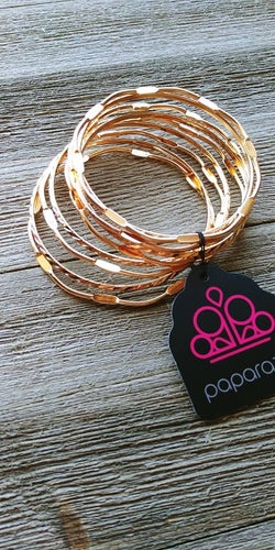 Featuring smooth and pressed faces, shimmery gold bangles stack across the wrist for a seasonal look.  Sold as one set of nine bracelets.  Always nickel and lead free.   Paparazzi Exclusive