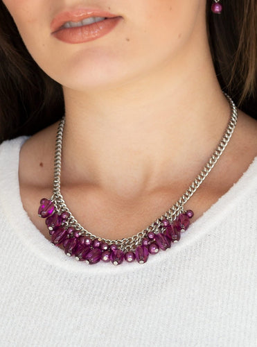 A collection of glassy and pearly purple beads dangle from the bottom of interconnected silver chains, creating a flirtatious fringe below the collar. Features an adjustable clasp closure.  Sold as one individual necklace. Includes one pair of matching earrings.  Always nickel and lead free.