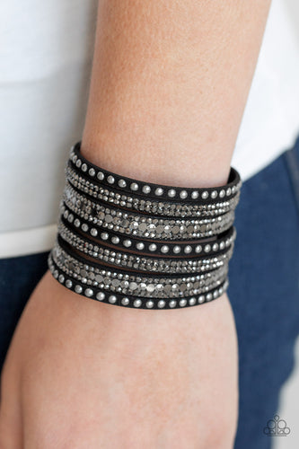 A thick black suede band has been spliced into glittery strands encrusted in a collection of dainty gunmetal studs, glittery hematite rhinestones, and flat gunmetal sequins for a sassy look. Features an adjustable snap closure.  Sold as one individual bracelet.  P9DI-URBK-199XX  Always nickel and lead free.