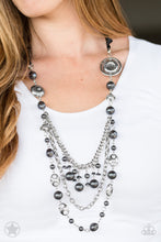 Load image into Gallery viewer, A silky black ribbon replaces a traditional chain to create a timeless look. Pearly dark gray beads and funky silver pieces intermix with varying lengths of silver chains to give a fresh take on a Victorian-inspired piece.  Sold as one individual necklace. Includes one pair of matching earrings.   Always nickel and lead free.
