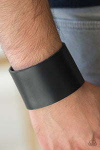 A thick black leather band wraps around the wrist for a bold urban look. Features an adjustable snap closure.  Sold as one individual bracelet.   Always nickel and lead free.