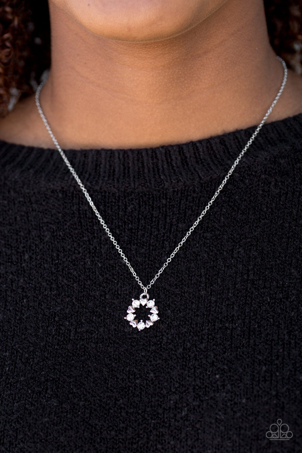 Dainty silver hearts and glittery white rhinestones join into a round dainty pendant below the collar for a romantic look. Features an adjustable clasp closure.  Sold as one individual necklace. Includes one pair of matching earrings.  Always nickel and lead free.