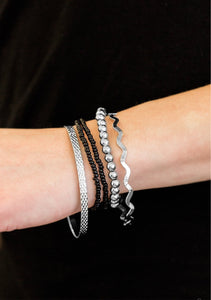 Varying in shimmer and shine, two silver bangles join a mishmash of stretchy silver and black beaded bracelets around the wrist for a seasonal look.  Sold as one set of five bracelets.   Always nickel and lead free.