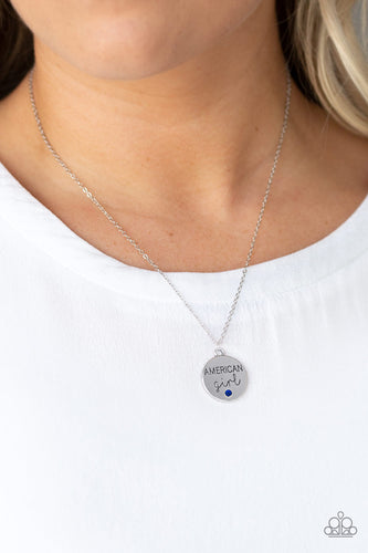 Dotted with a dainty blue rhinestone, a shimmery disc is stamped in the phrase,