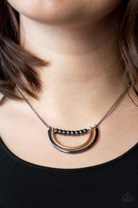 A strand of shiny gunmetal beads give way to bowing gold and gunmetal frames, creating an edgy pendant below the collar. Features an adjustable clasp closure.  Sold as one individual necklace. Includes one pair of matching earrings.  Always nickel and lead free.