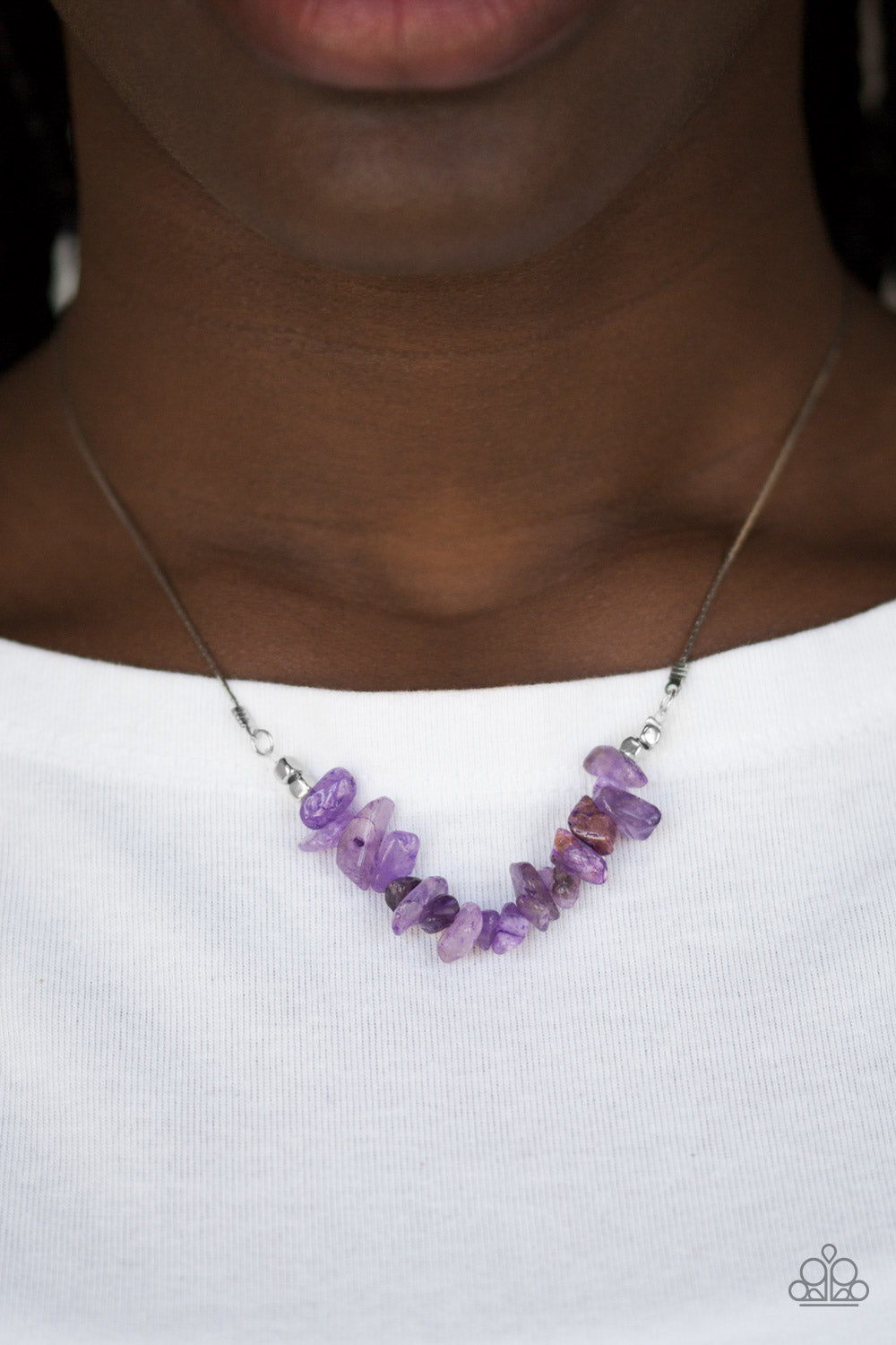 Attached to a dainty silver chain, bits of vivacious purple rock are threaded along an invisible wire below the collar for a seasonal look. Features an adjustable clasp closure.  Sold as one individual necklace. Includes one pair of matching earrings.  Always nickel and lead free.