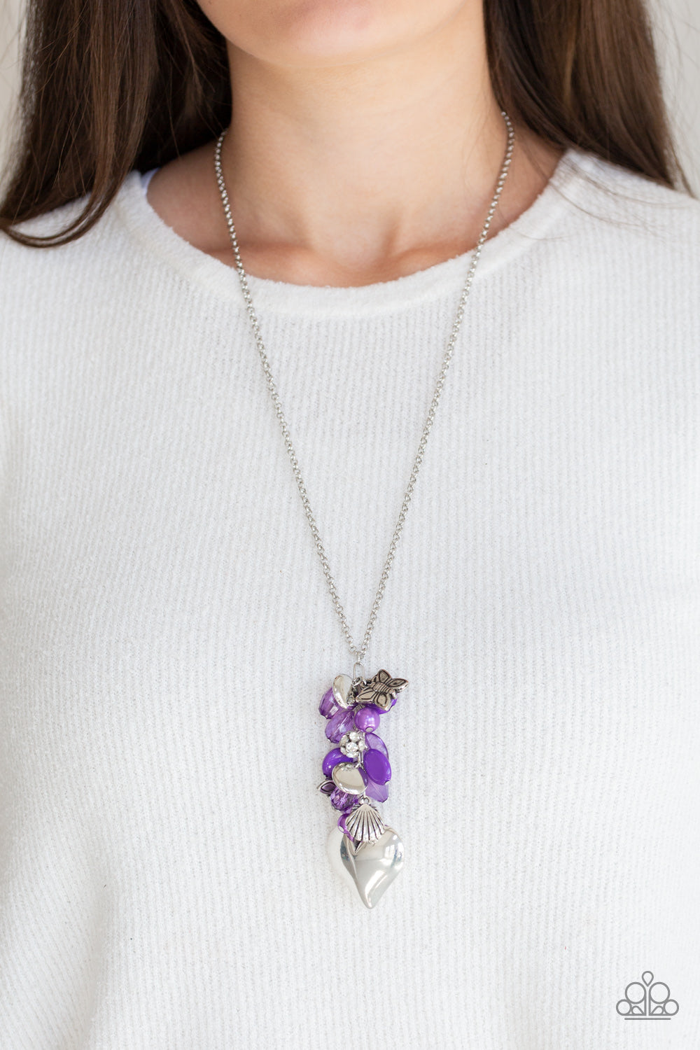 Infused with an array of purple beads, a collection of antiqued silver shell and butterfly charms trickle along the bottom of a shimmery silver chain. Complemented with glittery white rhinestone encrusted beads, a dramatically oversized silver heart pendant swings from the bottom of the clustered tassel for a whimsical finish. Features an adjustable clasp closure.  Sold as one individual necklace. Includes one pair of matching earrings.  Always nickel and lead free.