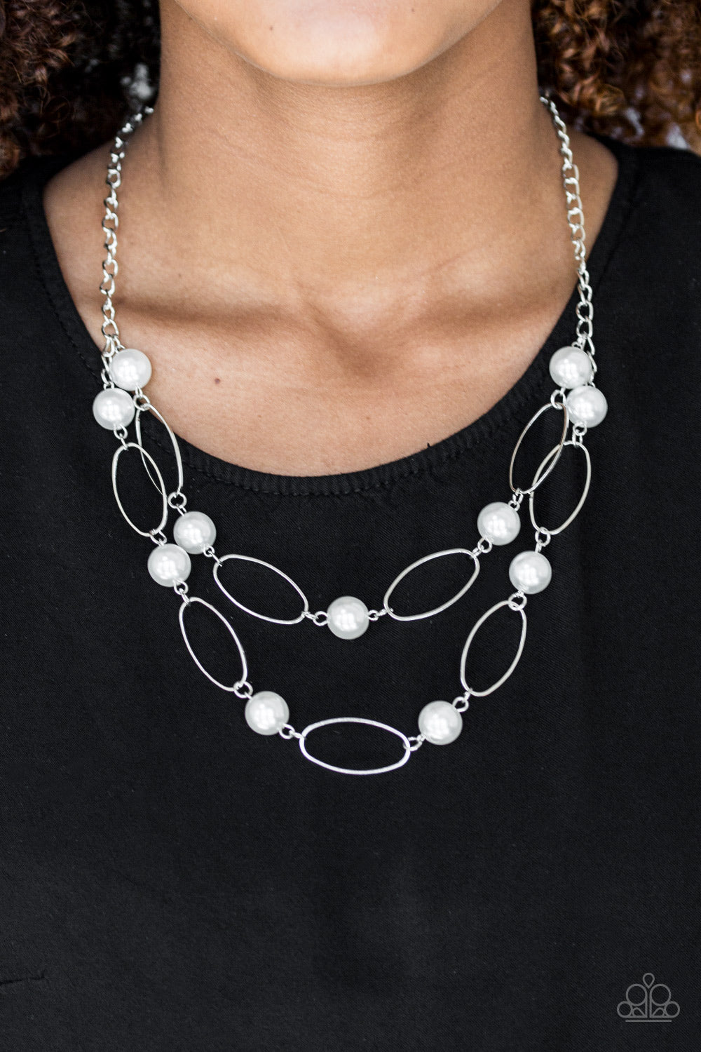 Two rows of white pearls and silver oval frames alternate below the collar, creating luminescent layers. Features an adjustable clasp closure.  Sold as one individual necklace. Includes one pair of matching earrings.  Always nickel and lead free.