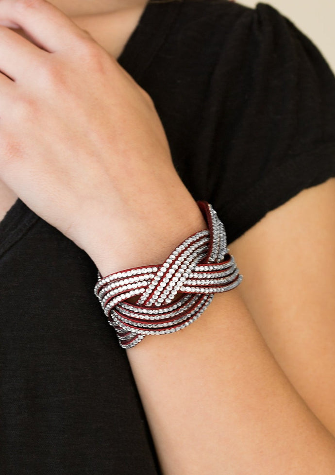 Glassy white rhinestones are encrusted along crisscrossing strands of red suede, creating bold shimmer around the wrist. Features an adjustable snap closure.  Sold as one individual bracelet.  Always nickel and lead free.