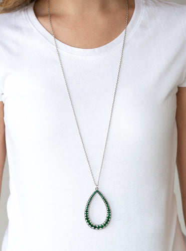 An oversized silver teardrop frame is encrusted in glittery green rhinestones that gradually increase in size at the bottom for a showstopping finish. The sparkling pendant swings from the bottom of a lengthened silver chain for a slimming finish. Features an adjustable clasp closure.  Sold as one individual necklace. Includes one pair of matching earrings.  Always nickel and lead free.