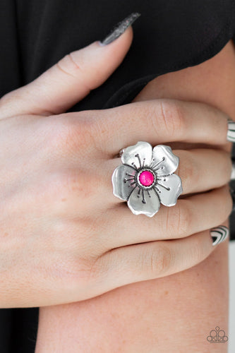 A bright pink bead is pressed into the center of a blooming silver flower radiating with antiqued details for a whimsical look. Features a stretchy band for a flexible fit.  Sold as one individual ring.  Always nickel and lead free.