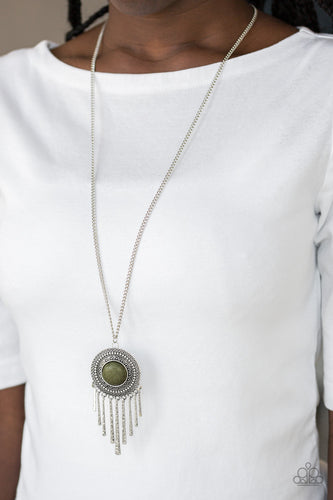 An earthy green stone is pressed into the center of a shimmery silver disc radiating with glistening tribal details. Swinging from the bottom of a lengthened silver chain, the bold pendant gives way to a fringe of delicately hammered silver rods for a wanderlust finish. Features an adjustable clasp closure.  Sold as one individual necklace. Includes one pair of matching earrings.  Always nickel and lead free.