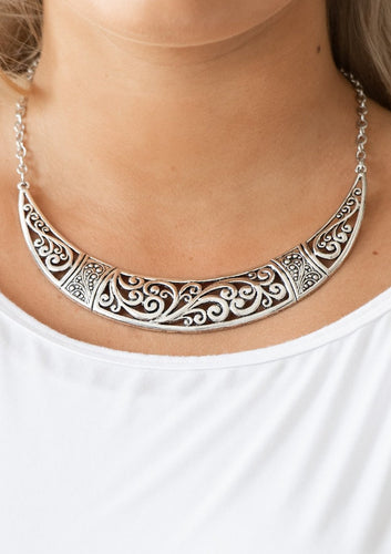 Swirling with ornate filigree filled detail, a shimmery silver crescent plate swings below the collar for a fierce look. Features an adjustable clasp closure.  Sold as one individual necklace. Includes one pair of matching earrings.  Always nickel and lead free.