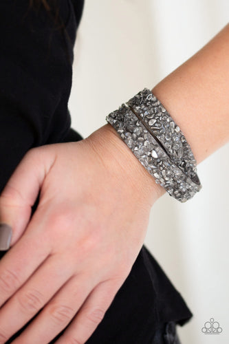 A collection of crushed rocks and glassy rhinestone prisms are sprinkled across a gray suede band for a seasonal look. The elongated band allows for a trendy double wrap design. Features an adjustable snap closure.  Sold as one individual bracelet.  Always nickel and lead free.