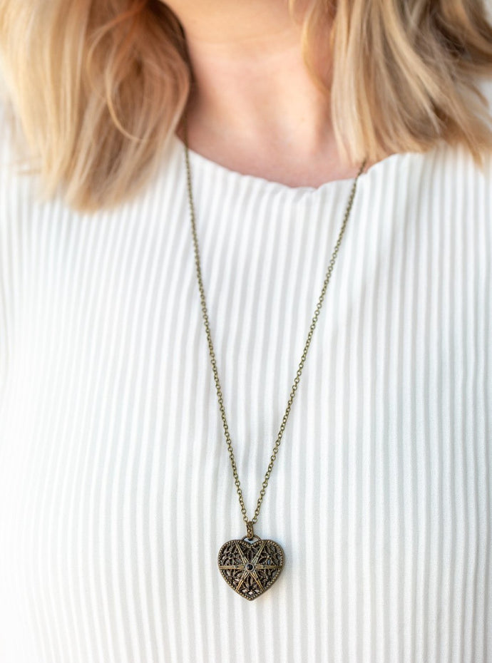Encrusted in glittery black rhinestones, a vintage inspired heart pendant swings from the bottom of a shimmery brass chain for a romantic fashion. Features an adjustable clasp closure.  Sold as one individual necklace. Includes one pair of matching earrings.  Always nickel and lead free.