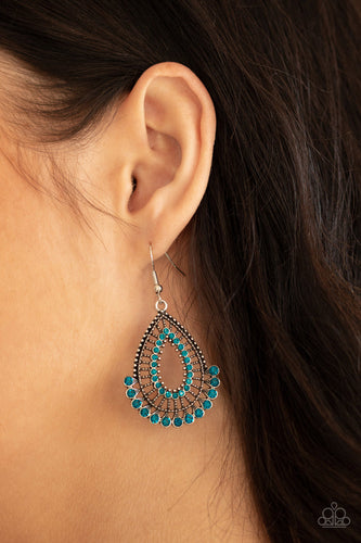 A fan of blue rhinestones flares out from the bottom of an ornately studded silver teardrop featuring an airy blue rhinestone ringed center. Earring attaches to a standard fishhook fitting.  Sold as one pair of earrings.  Always nickel and lead free.