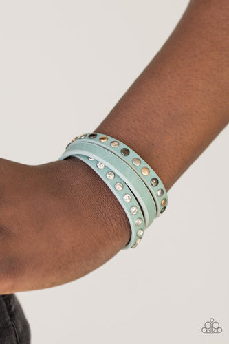 A skinny strip of blue leather is encrusted in sections of glittery white rhinestones and flat gold, gunmetal, and silver studs. The elongated band double wraps around the wrist for a fierce one-of-a-kind look. Features an adjustable snap closure.  Sold as one individual bracelet.  Always nickel and lead free.