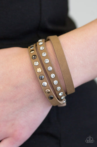 A skinny strip of brown leather is encrusted in sections of glittery white rhinestones and flat gold, gunmetal, and silver studs. The elongated band double wraps around the wrist for a fierce one-of-a-kind look. Features an adjustable snap closure.  Sold as one individual bracelet.  Always nickel and lead free.
