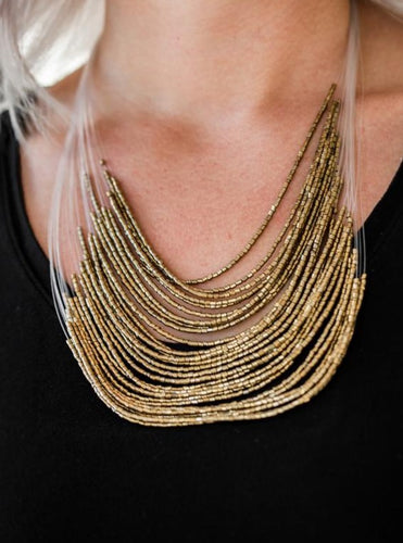 Strand after strand of shimmering brass seed beads fall together to create a bold statement piece. Features an adjustable clasp closure.  Sold as one individual necklace. Includes one pair of matching earrings.