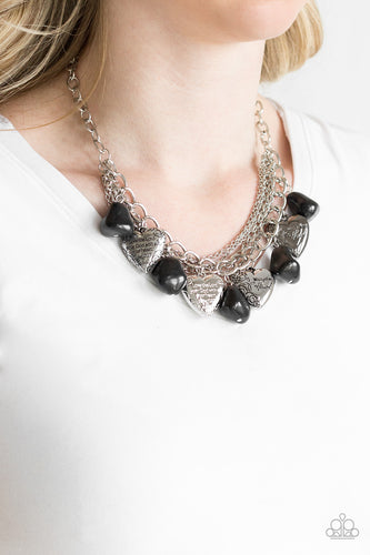 Black faux rocks alternate with heart charms along a chunky silver chain. Hearts are inscribed with the phrase