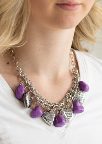 Purple faux rocks alternate with heart charms along a chunky silver chain. Hearts are inscribed with the phrase