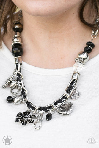 Black and ivory cording is braided through a chunky silver chain. A unique variety of charms decorate the piece including a delicate flower and a heart. Heart is inscribed with the phrase
