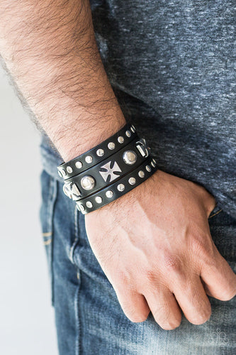 Bold metallic accents and silver studs are encrusted along a thick black leather band that has been spliced into three strands for a rugged look. Features an adjustable snap closure.  Sold as one individual bracelet.  Always nickel and lead free.