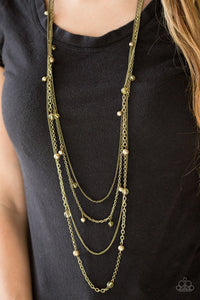 Varying in shape and shimmer, four glistening brass chains drape across the chest. Glassy and pearly brass beading alternate along the shimmery layers for a refined finish. Features an adjustable clasp closure.  Sold as one individual necklace. Includes one pair of matching earrings.  Always nickel and lead free.