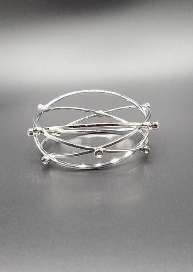 Featuring raised silver rhinestones on a crisscross pattern design, the silver bangle glide across the wrist for a sleek look.  Sold as one individual bracelet.  Always nickel and lead free.