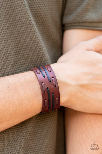 Brown and black leather laces are haphazardly threaded through a thick brown leather band, creating a rustic display around the wrist. Features an adjustable snap closure.  Sold as one individual bracelet.  Always nickel and lead free.