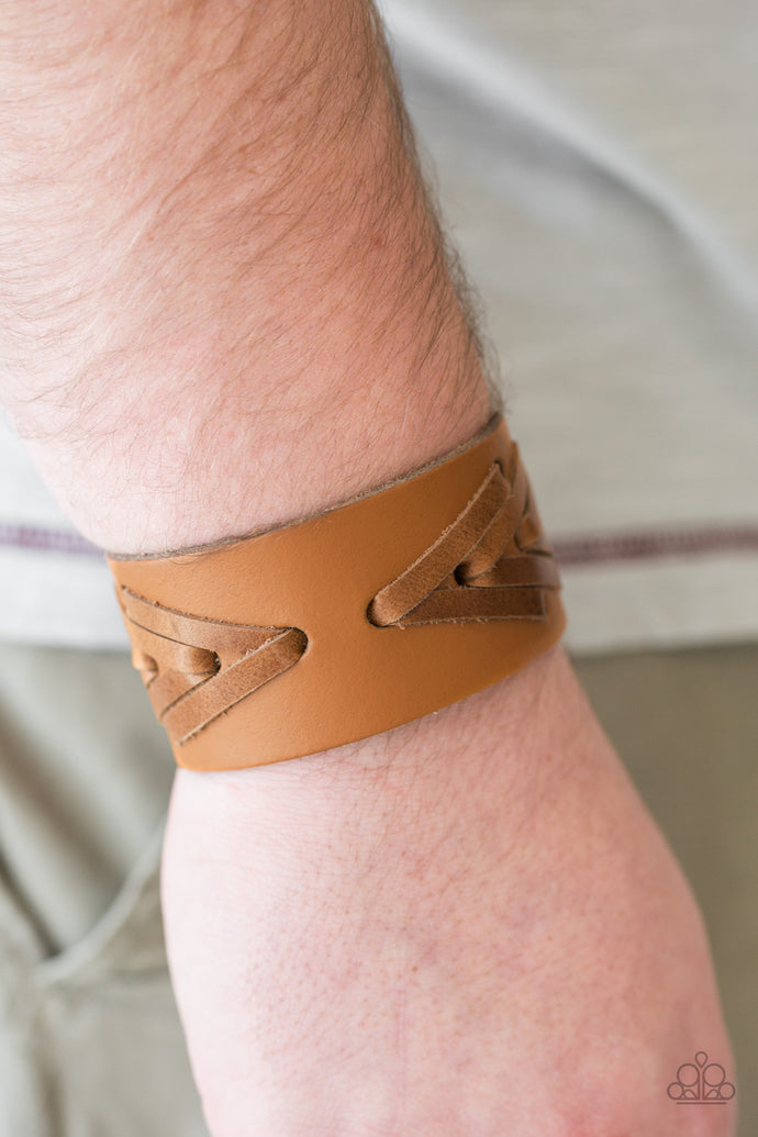 Strips of distressed leather laces are stitched across the front of a leather band, creating a rugged geometric pattern around the wrist. Features an adjustable snap closure.  Sold as one individual bracelet.  Always nickel and lead free.