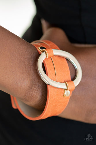 An oval silver ring loops through two belt loop fittings and is studded in place across the front of a spliced orange leather band for a bold urban look. Features an adjustable snap closure.  Sold as one individual bracelet. Always nickel and lead free.