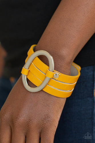 An oval silver ring loops through two belt loop fittings and is studded in place across the front of a spliced yellow leather band for a bold urban look. Features an adjustable snap closure.